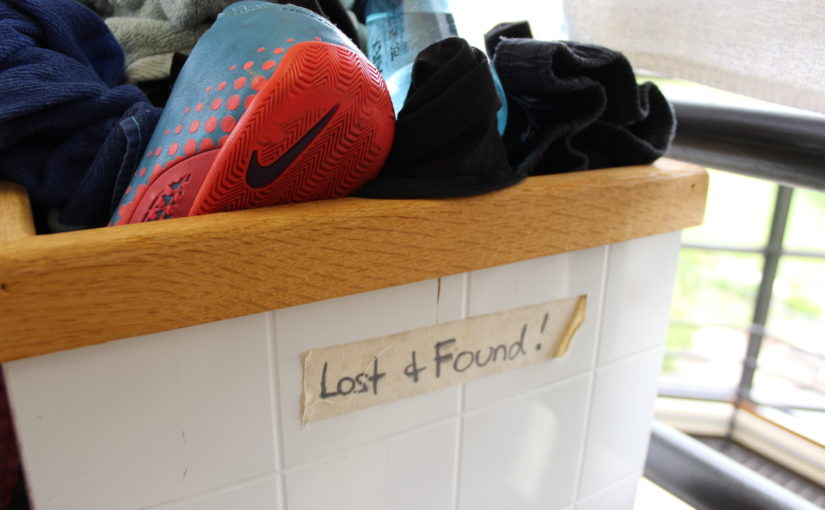 Photo of lost and found bin stuffed with clothes, shoes, and a water bottle.