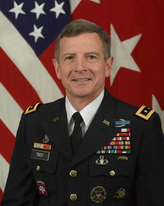 Headshot of Lt. General William Troy in uniform with stars and stripes in the background.