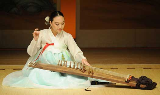 "A photo of Jen Shyu plays ""gayageum,"" a traditional Korean zither-like instrument."