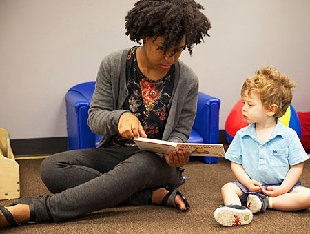 A photo of Lawrence University student shares a story with a toddler at the Community Early Learning Center.
