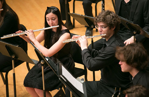 A photo of Lawrence University students playing flute in a concert.