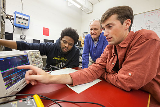 A photo of Lawrence University physics professor Matthew Stoneking and students observing different waves on the monitor screen.