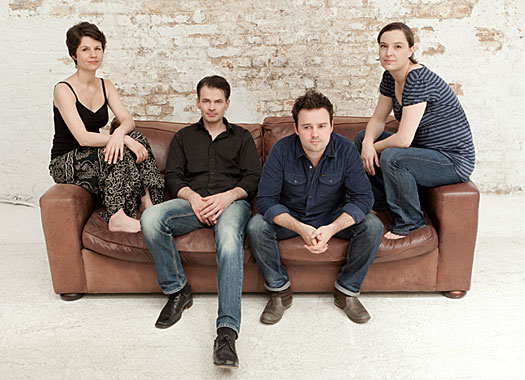 A photo of London-based Elias String Quartet sitting on the couch.