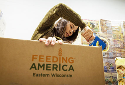 A photo of Lawrence University student packing up a box to send to Feeding American in Eastern Wisconsin.