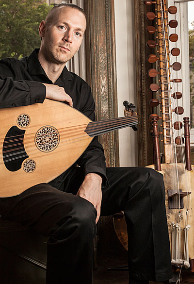 A photo of Kane Mathis with a Turkish oud and a 21-string kora.