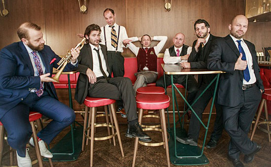 A group photo of members of Mnozil Brass sitting on stools