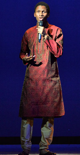 A black student singing wearing traditional African clothing.