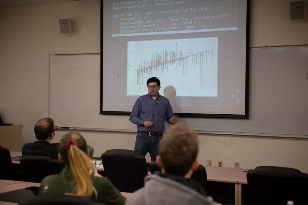 Professor Arnold Shober stands in front of a graph in a classroom.