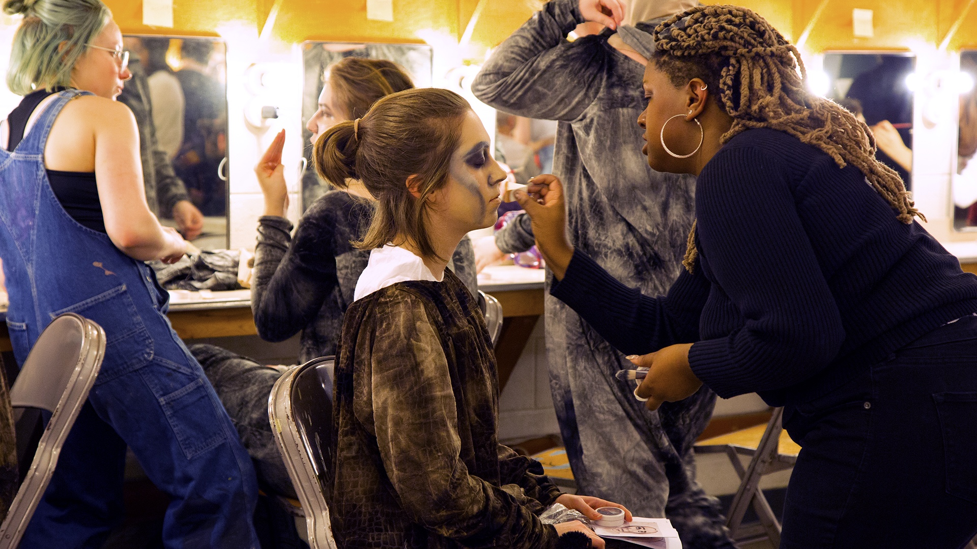 A cast member gets makeup applied before rehearsal.