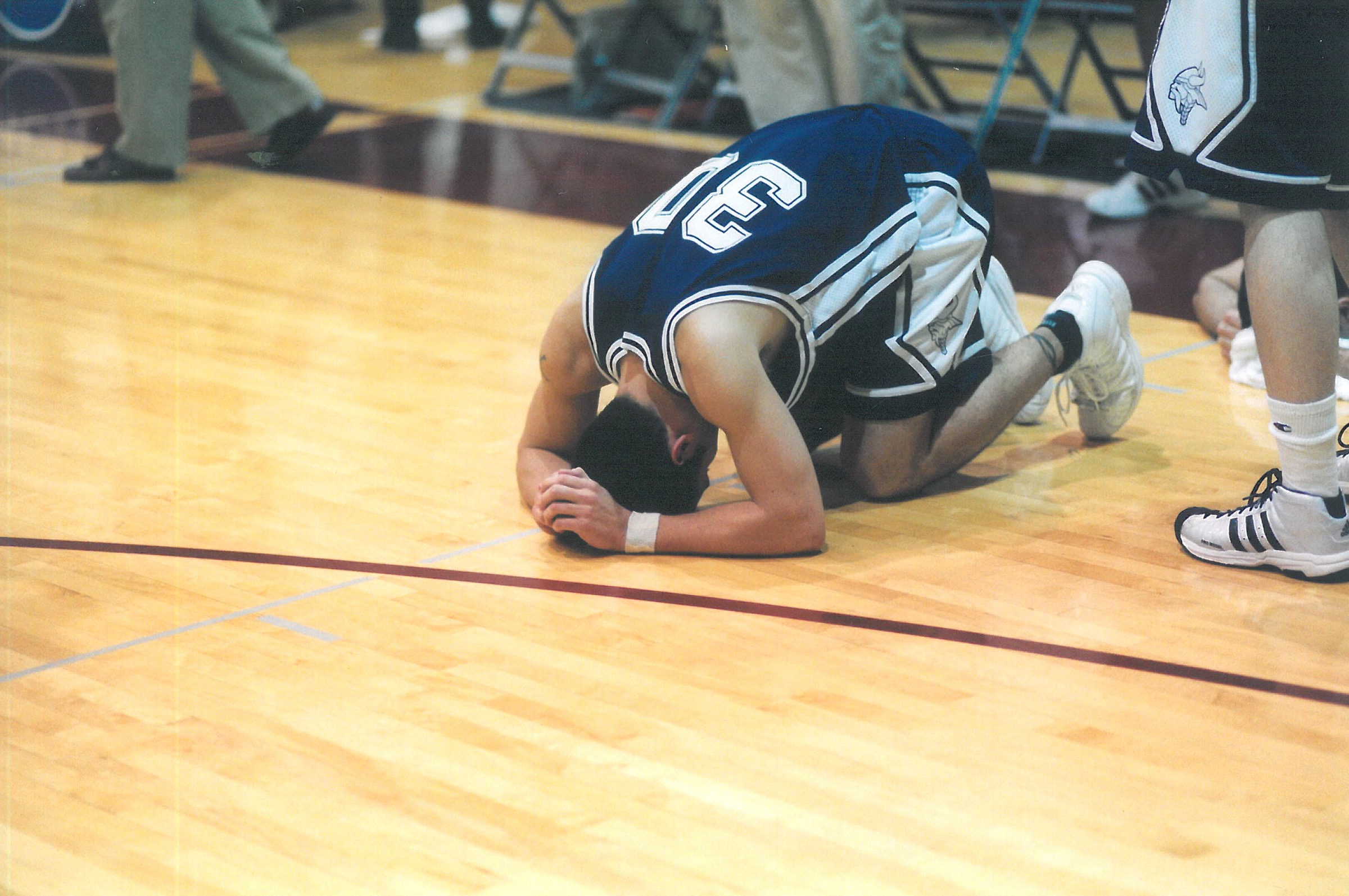 Rob Nenahlo buries his head as he falls to the floor at the end of the game against UW-Stevens Point.