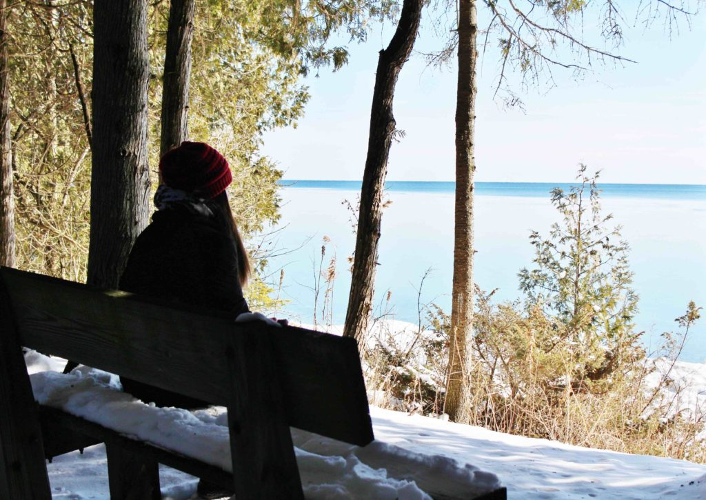 A student participating in a Deep Listening retreat at Bjorklunden during the winter sits on a bench looking out at the lake.