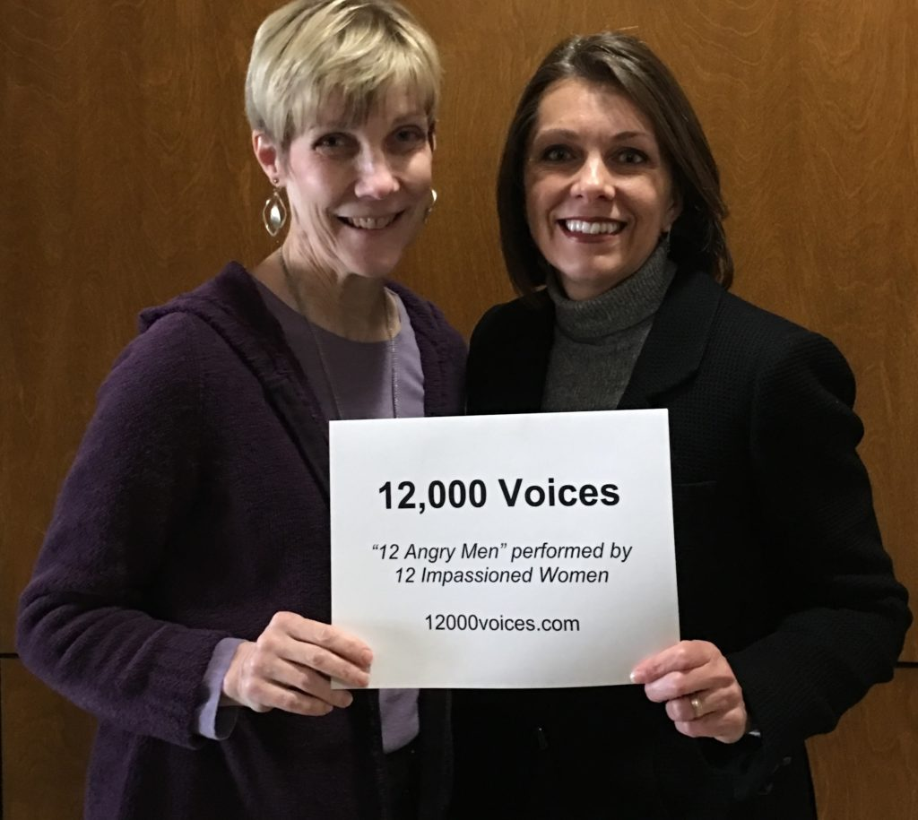 Kathy Privatt and Maria Van Laanen hold a 12,000 Voices sign.
