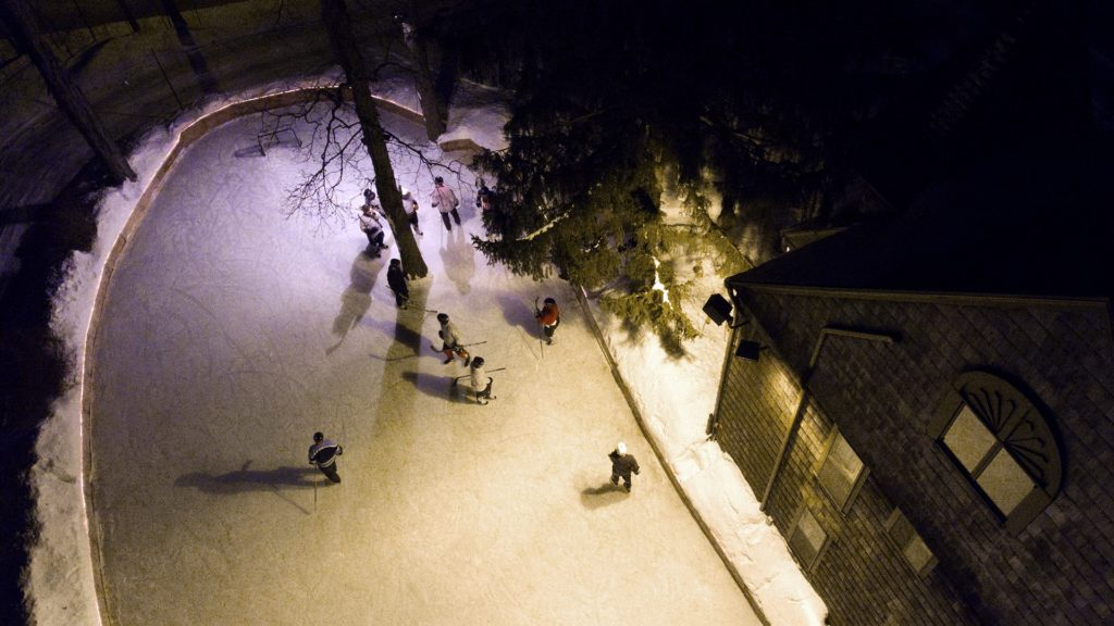 Aerial view of hockey players making their way across the ice on the McKee outdoor rink.
