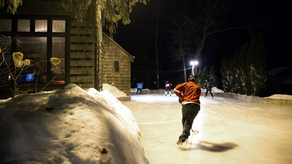 A player brings the puck up the ice during a Tuesday night game at the McKee outdoor rink.