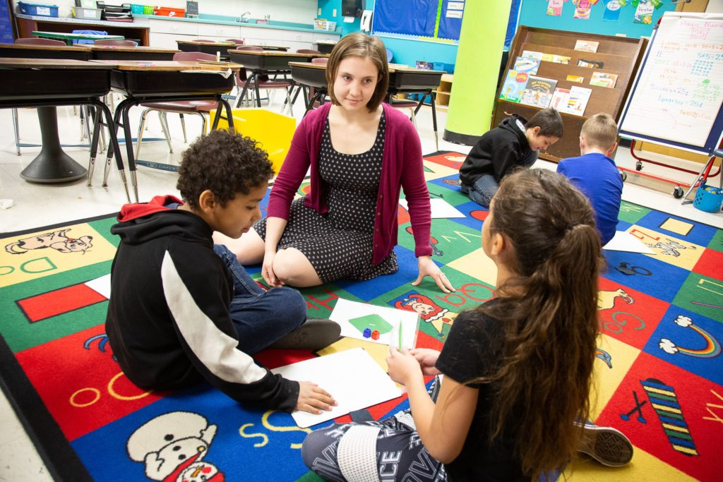 Michelle Gibson sits on the floor with some of her second-grade students during a class project at Lincoln Elementary School.
