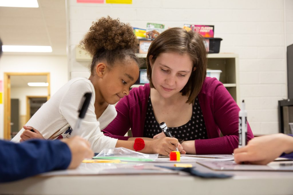 Michelle Gibson '17 works at a table with a second-grader at Lincoln Elementary School in Appleton.