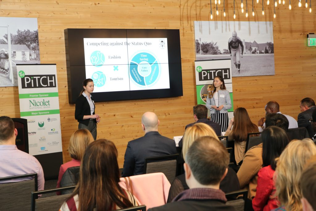 Katie Kitzinger '20, left, and Emma Liu '19 present Jetsetter's Closet to a panel of judges and an audience at the third-annual The Pitch, held at Titletown Tech in Green Bay.