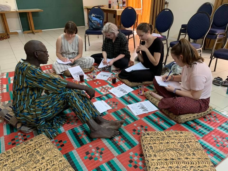 The Lawrence students sit on the floor during a session with an instructor in the Baobab Center in Dakar.