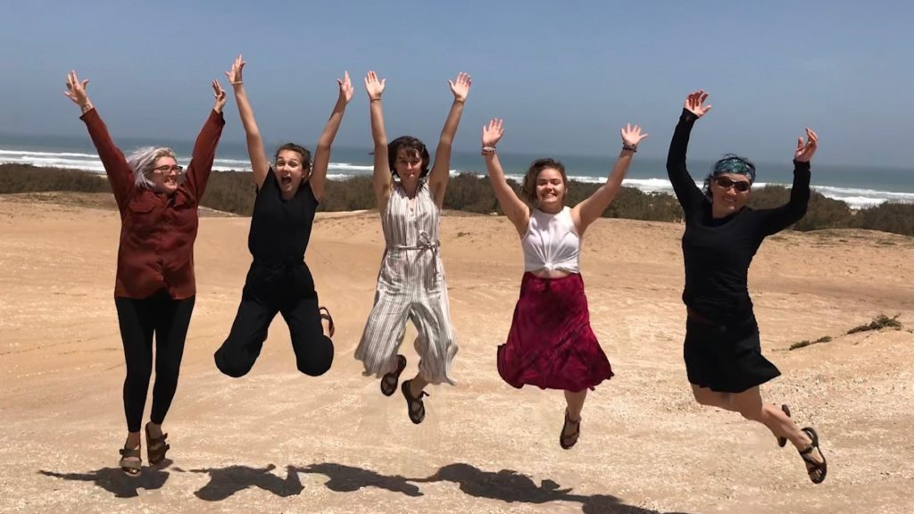 Dominica Chang and Lawrence students Bronwyn Earthman, Mima Tabishat, Miriam Thew-Forrester, and Greta Wilkening jump in the air at Lac Rose along the Atlantic Ocean just outside of Dakar.