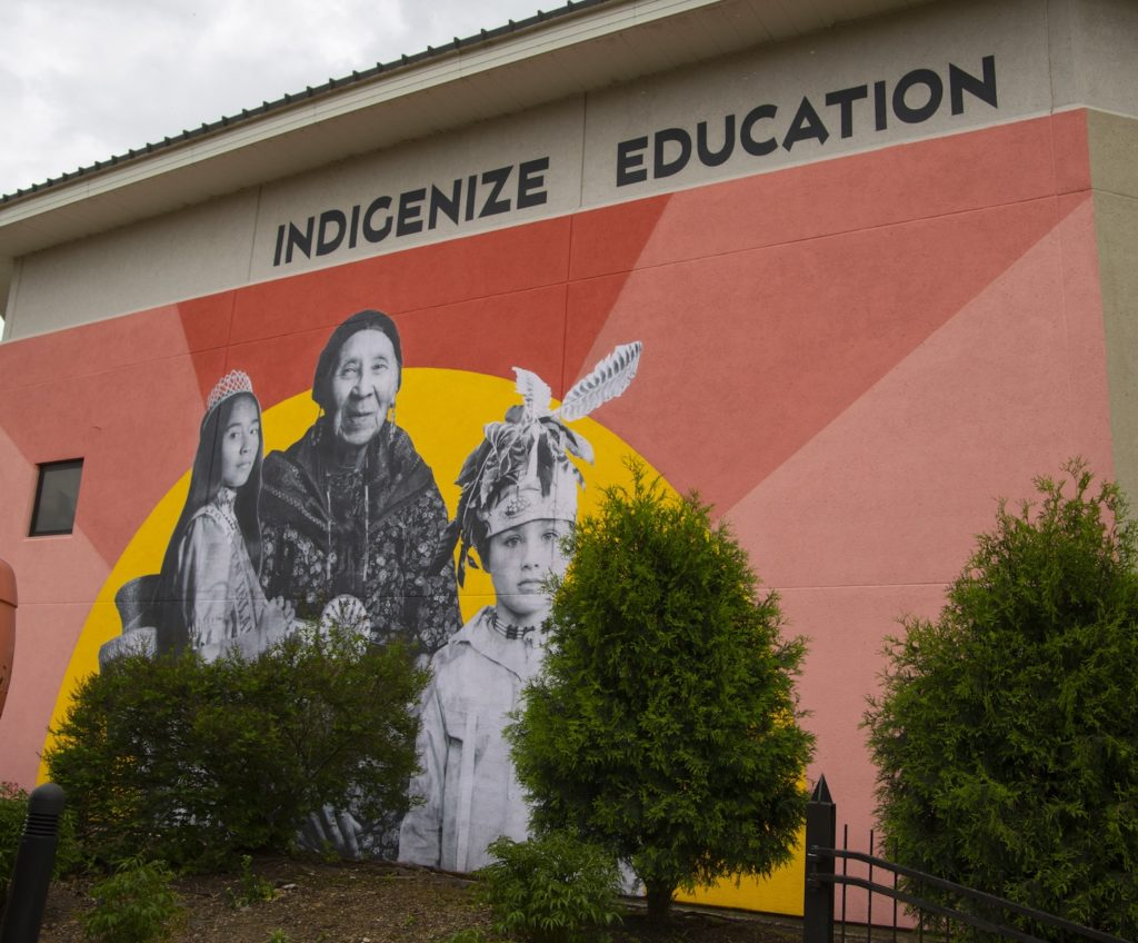 Photo of the Project 562 mural on the exterior wall of the Buchanan Kiewit Wellness Center featuring a pink and yellow sunset with photos of local tribal members in traditional regalia overlaying the sun.