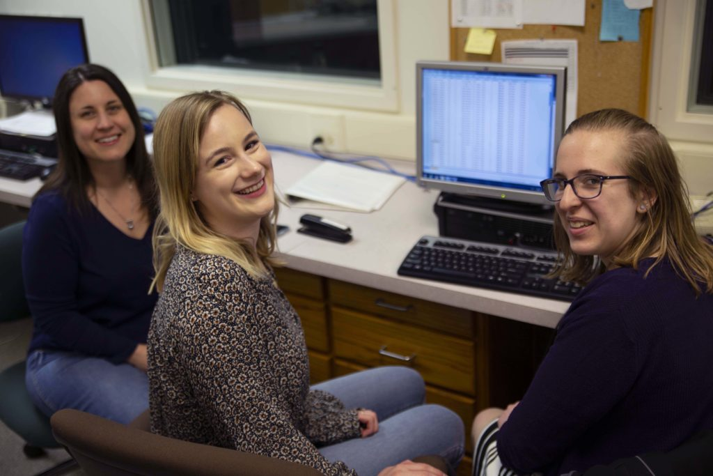 Lori Hilt, Caroline Swords and Sara Prostko pose for a photo in the psychology department.