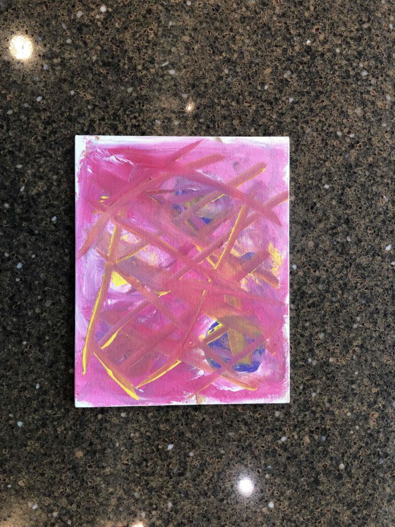 Photo of small painting featuring what appears to be planets covered in pink smears of paint.