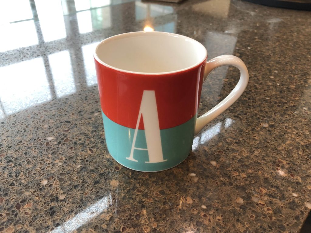 "Photo of red and blue coffee mug featuring the letter ""A."""