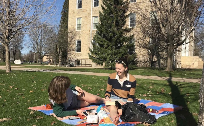 Two female Lawrence students study on a blanket in the grass in front of Main Hall.