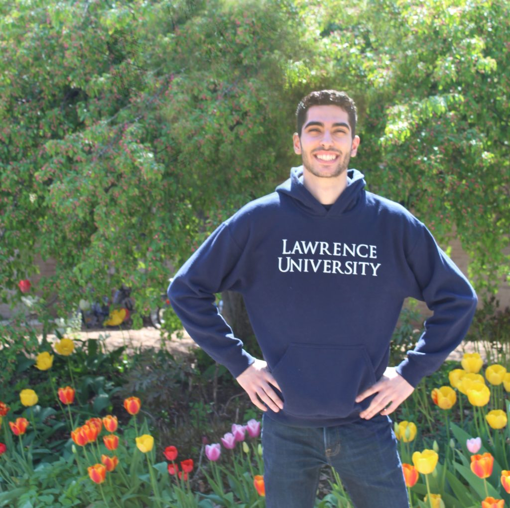 Male Lawrence student wearing navy blue Lawrence University hooded sweatshirt.