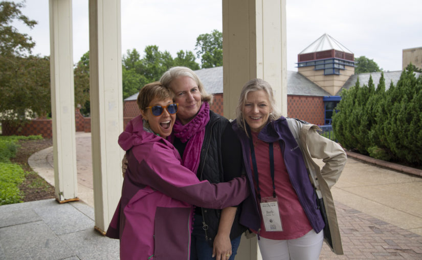 Three alumni hug during reunion weekend.