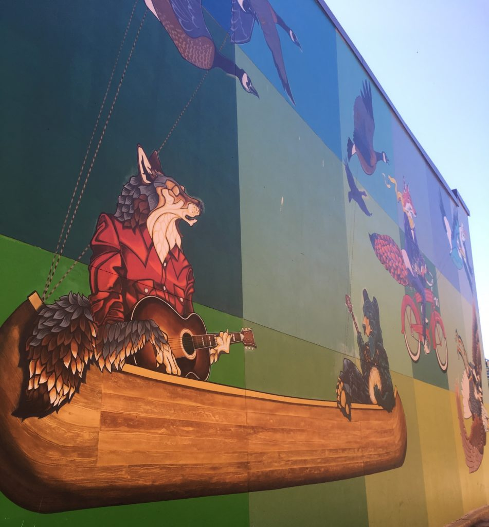 Photo of colorful mural located in downtown Appleton, Wisconsin featuring a wolf in a boat, a fox on a bike, and other personified creatures in action.