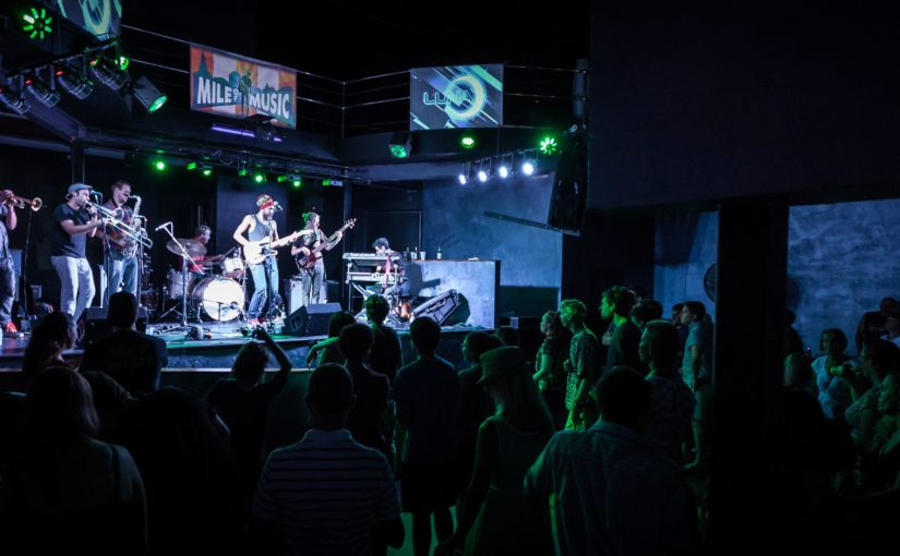 Photo of a band with guitars, drums, and horns playing in front of a crowd at the Mile of Music.