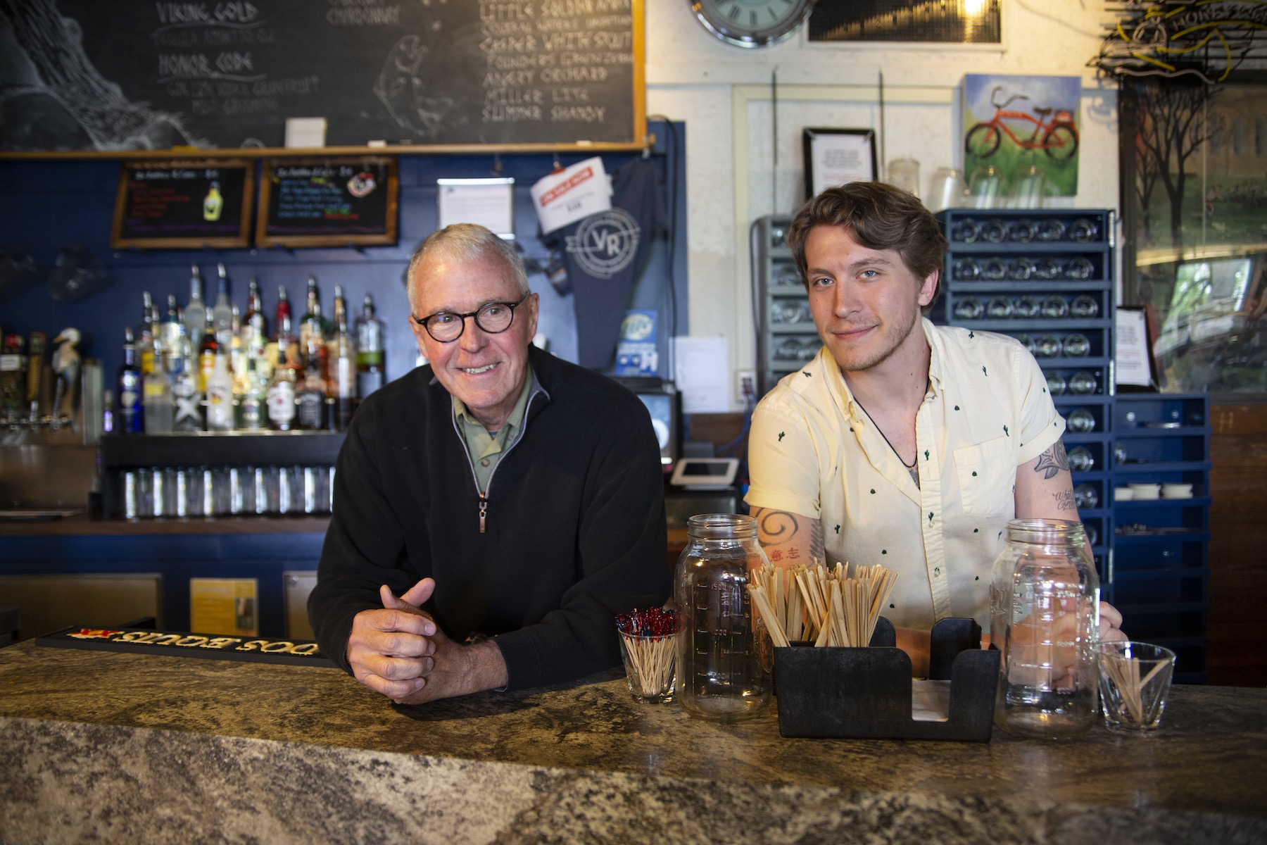 Mark Catron '69, a student bartender when the Viking Room opened as a bar in 1969, stands behind the bar with Jake Yingling '20 during Reunion Weekend.