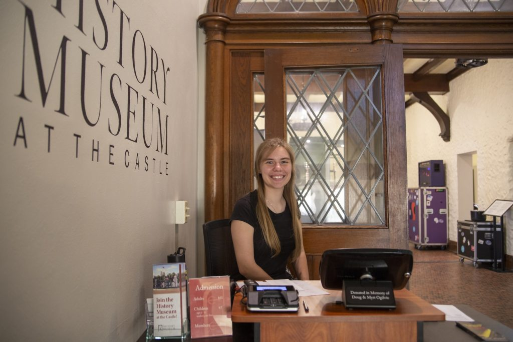Johanna Kopecky '21 sits at the front desk of the History Museum at the Castle in downtown Appleton.