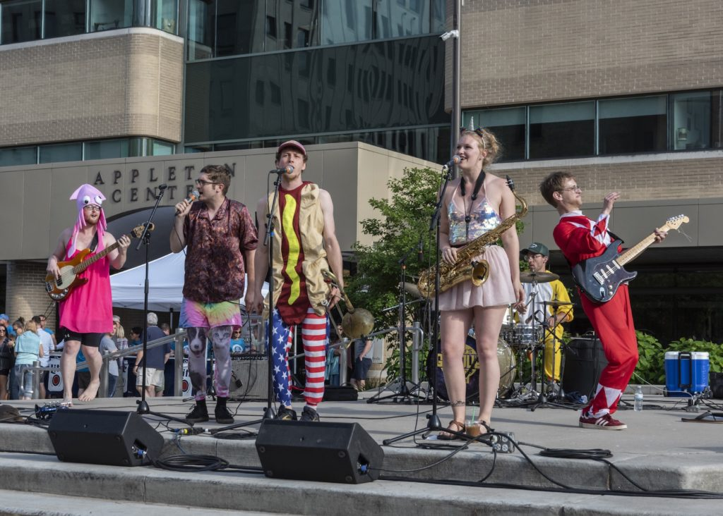 Porky's Groove Machine, wearing wildly random costumes, perform on stage at Houdini Plaza.