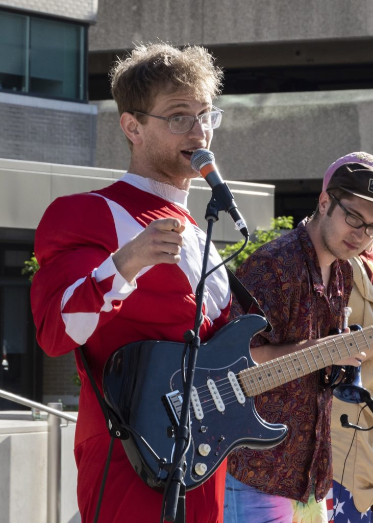 Ilan Blanck wears a red Power Ranger suit while performing at Houdini Plaza.