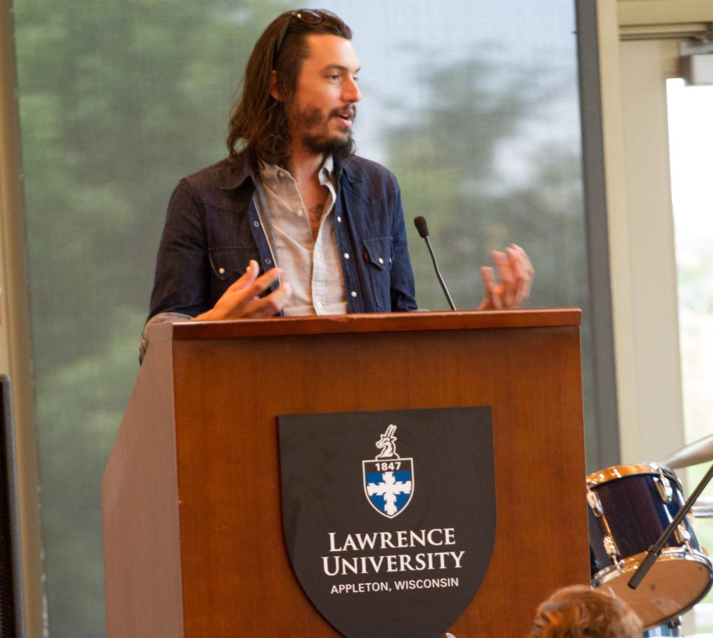 Cory Chisel speaks at the podium during Lawrence's 2015 Report to the Community. He received a collaboration award for Mile of Music.