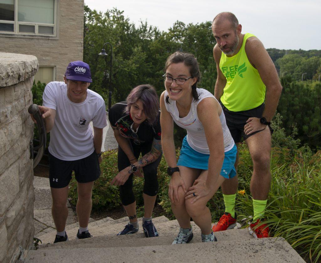 Douglas Martin, Megan Pickett, Relena Del Toro Ribbons, and Jason Brozek pose on campus in their running gear.