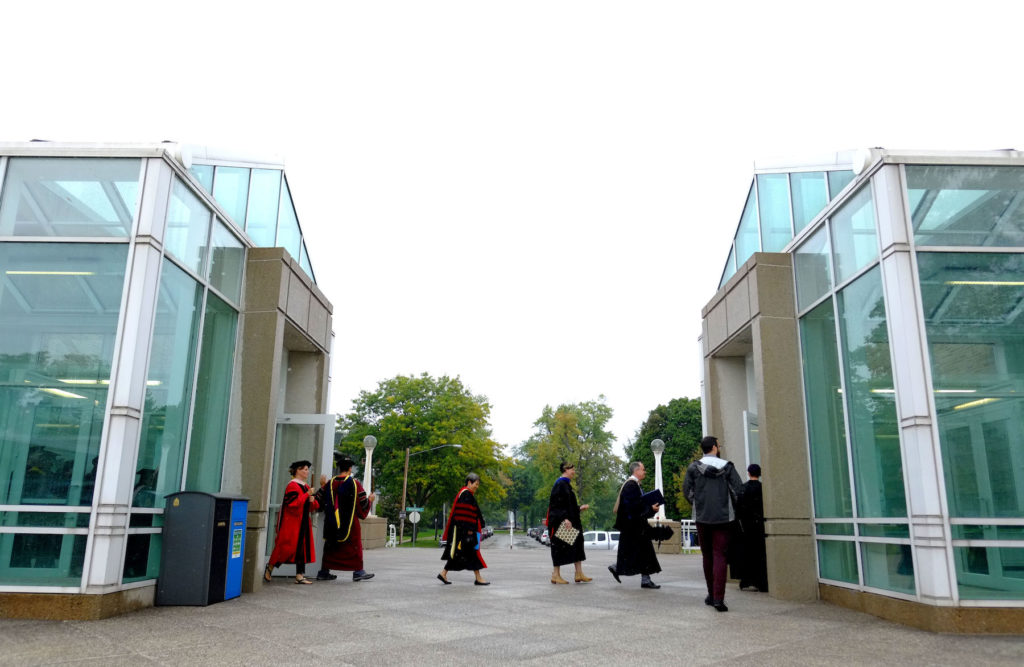Faculty members, adorned in their academic dress, proceed from the Music-Drama Center to Memorial Chapel on Thursday.