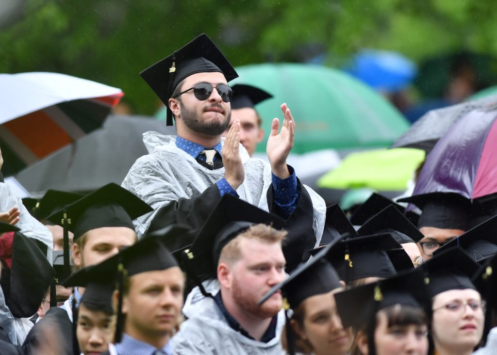 A graduate stands and applauds during Lawrence's 2019 commencement ceremony in June.