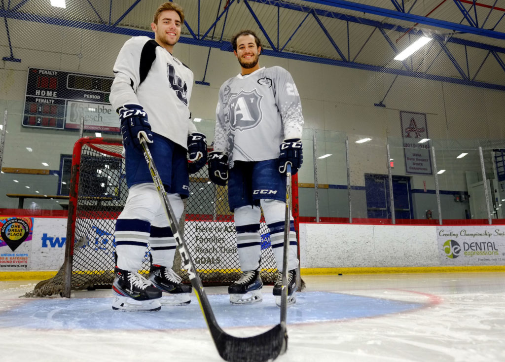 Jordan Boehlke and Danny Toycen stand in front of the net on a hockey rink at Appleton Family Ice Center.