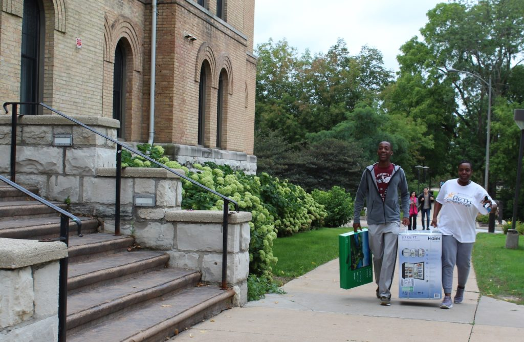 Students carry their things into Ormsby Hall.