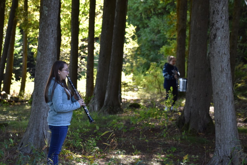 Lawrence students play their instruments amid the trees on the Bjorklunden property.