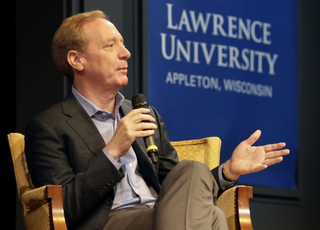Microsoft President Brad Smith sits in a chair on stage as he talks with the audience in Stansbury Theatre.