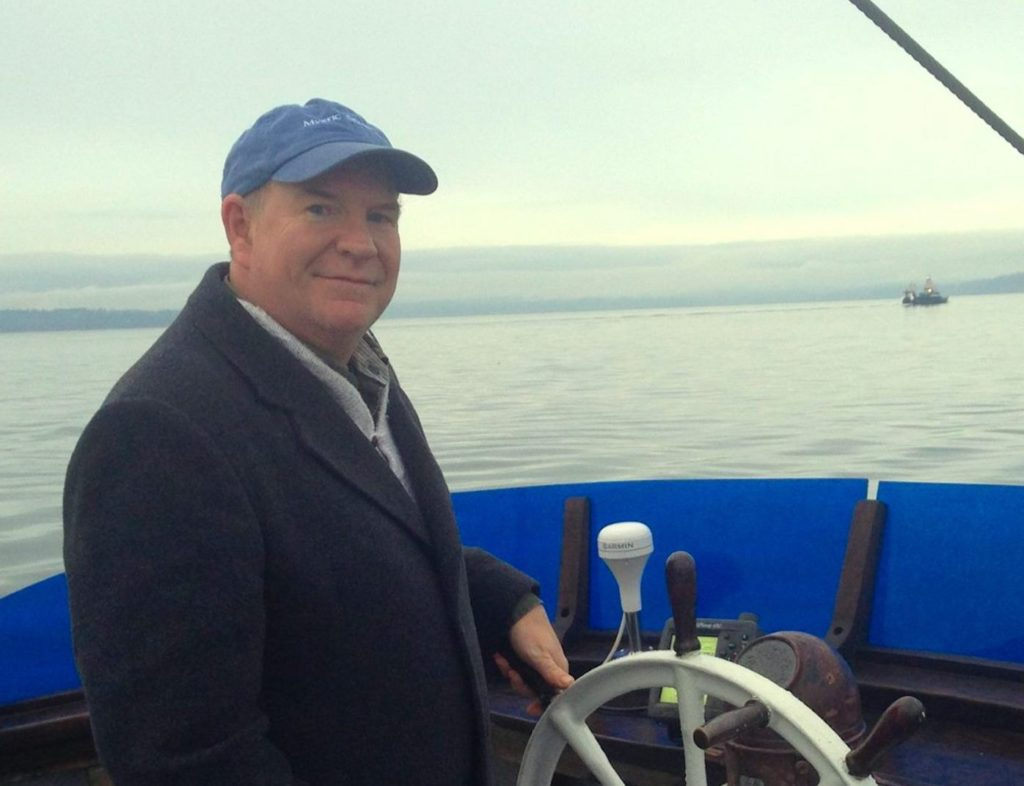 John Odin Jensen '87 poses for a publicity photo at the wheel of a ship.