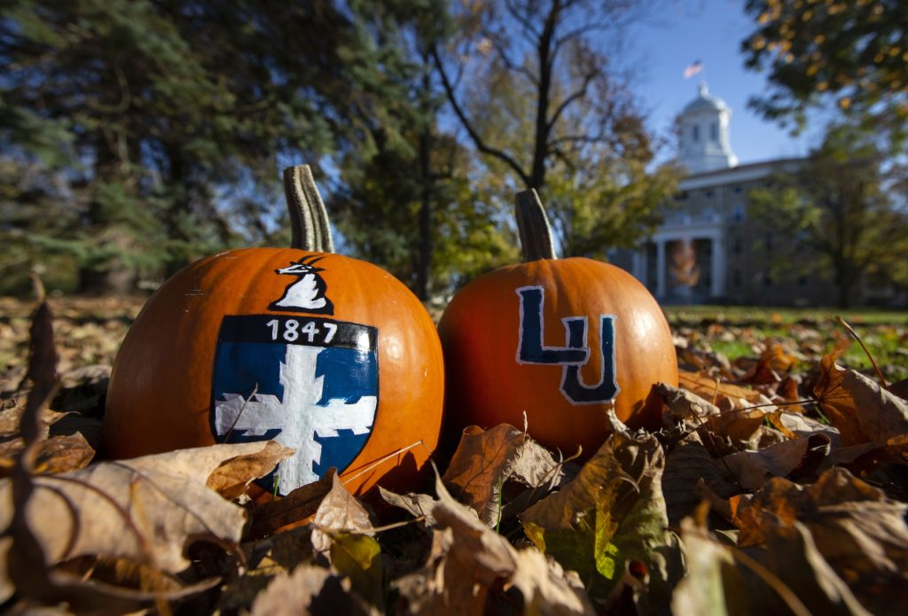 Two pumpkins with Lawrence logos painted on them rest among the leaves on Main Hall Green.