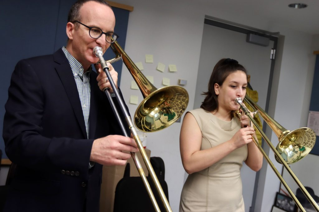 Tim Albright, assistant professor of music, and junior Allie Goldman play trombones during a teaching session Thursday in Shattuck Hall of Music.
