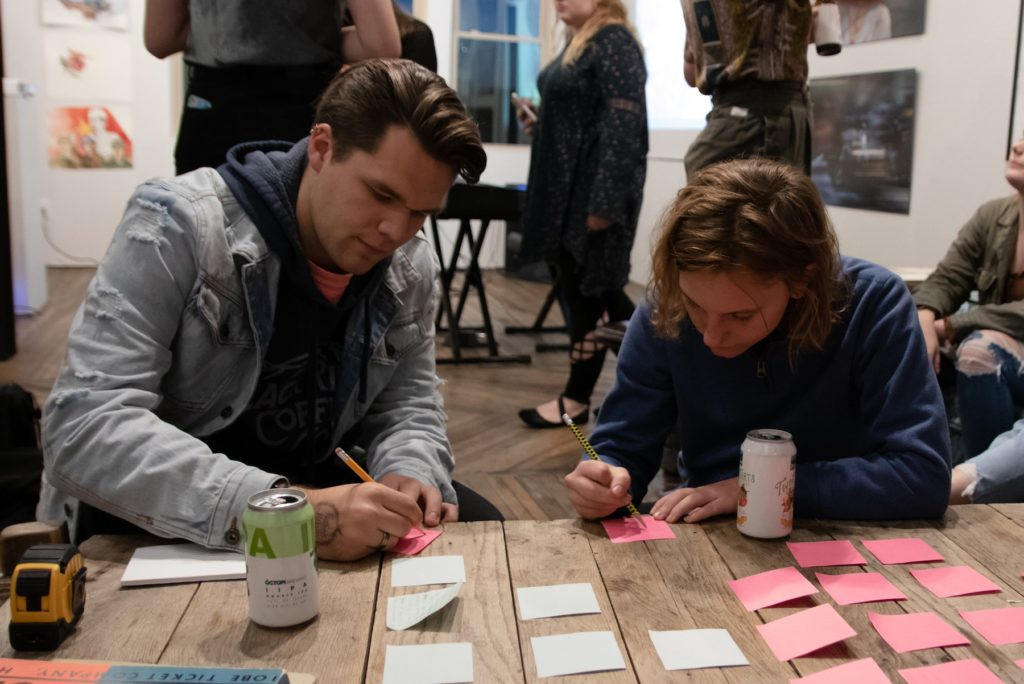 "Two participants fill out Post-it Notes as part of a ""Stories From Home"" theme at a recent Pop the Bubble event."