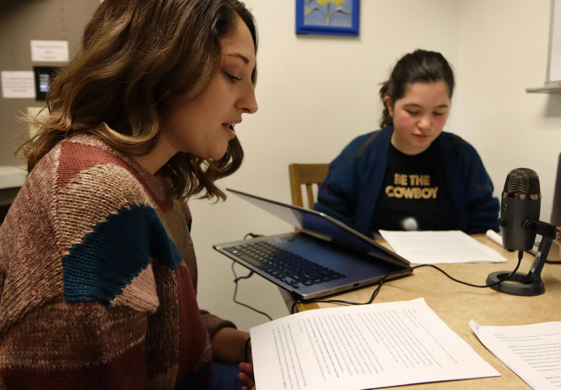 Fallon Sellers and Georgia Greenberg sit at a table with a microphone as they record a podcast for their War and Pop Culture class.