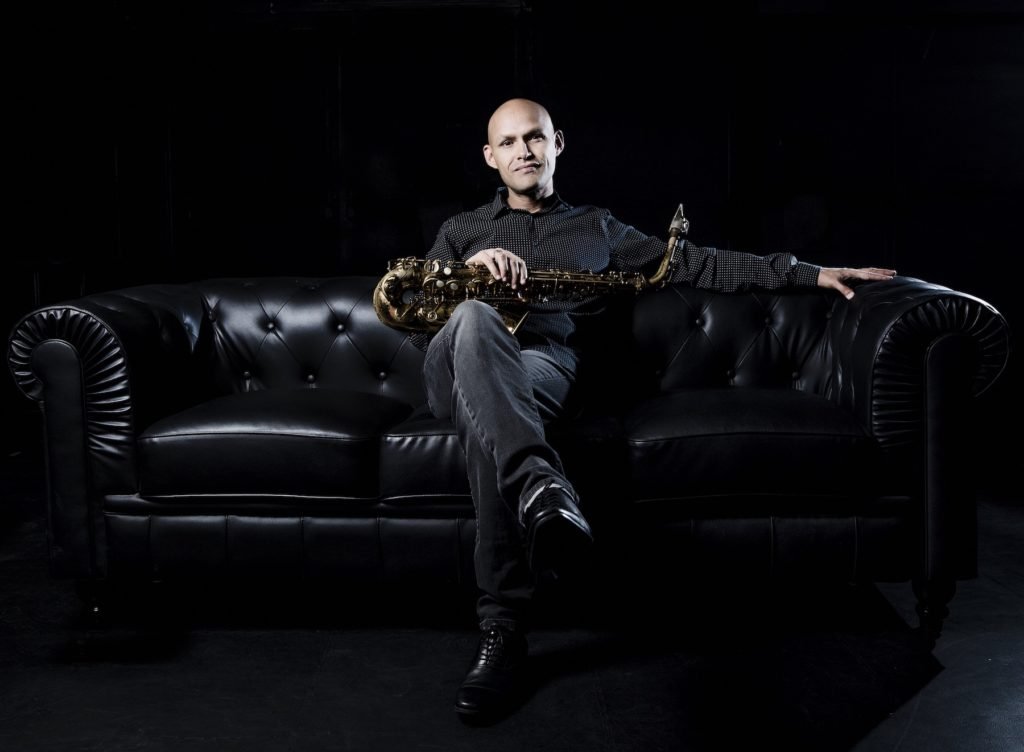 Portrait of Miguel Zenon sitting with his saxophone.
